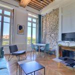 LMNP avantages-salon meublé cheminée mur en pierre parquet grandes fenêtres