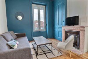 location meublée non professionnel-salon meublé cheminée murs bleu tapis parquet